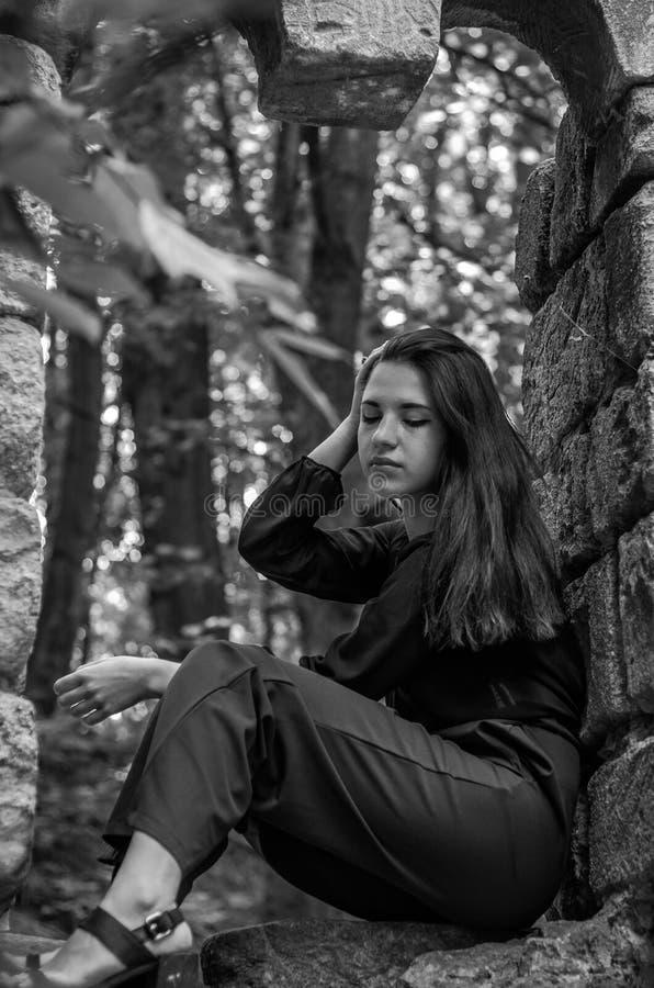 Menina encantador nova o adolescente com o cabelo longo que senta-se nas ruínas tristes de uma janela de pedra antiga do castelo  imagens de stock royalty free