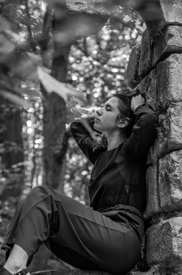 Menina encantador nova o adolescente com o cabelo longo que senta-se nas ruínas tristes de uma janela de pedra antiga do castelo  fotos de stock royalty free