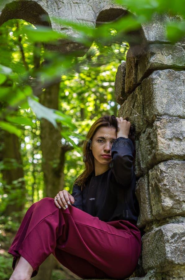 Menina encantador nova o adolescente com o cabelo longo que senta-se nas ruínas tristes de uma janela de pedra antiga do castelo  fotografia de stock royalty free