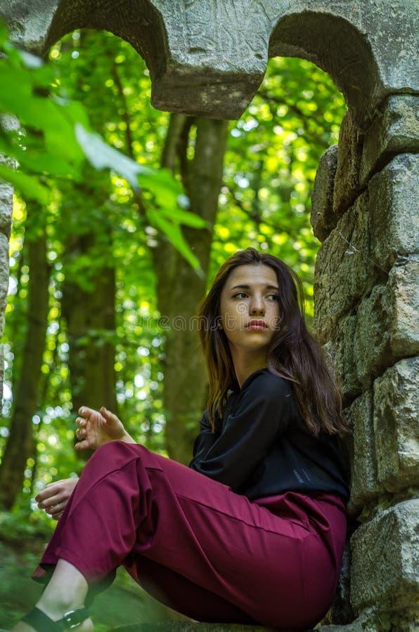Menina encantador nova o adolescente com o cabelo longo que senta-se nas ruínas tristes de uma janela de pedra antiga do castelo  foto de stock