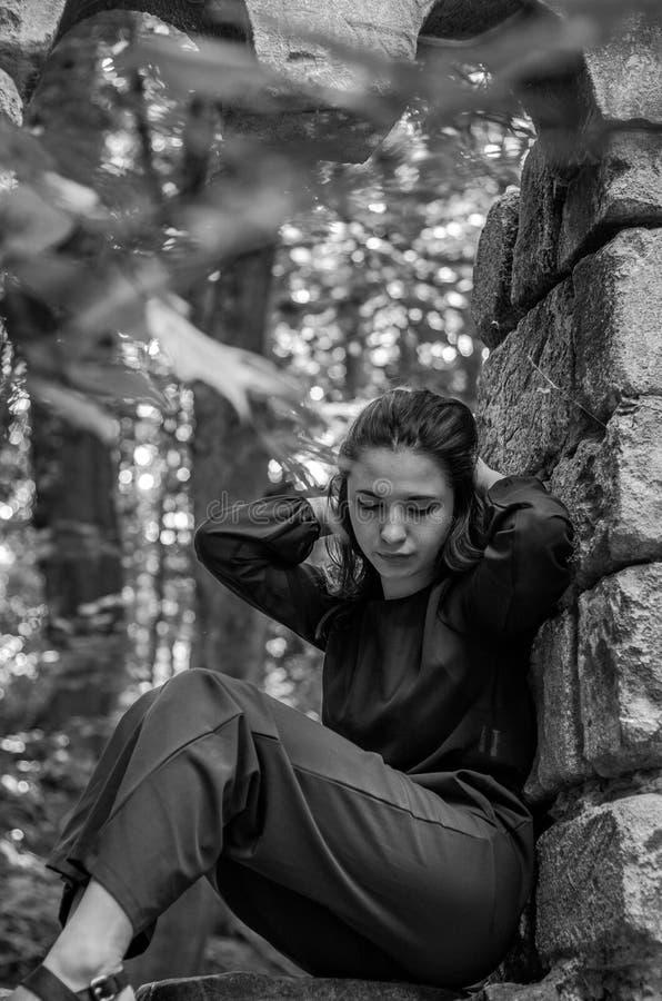 Menina encantador nova o adolescente com o cabelo longo que senta-se nas ruínas tristes de uma janela de pedra antiga do castelo  fotos de stock