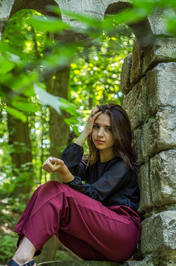 Menina encantador nova o adolescente com o cabelo longo que senta-se nas ruínas tristes de uma janela de pedra antiga do castelo  imagens de stock