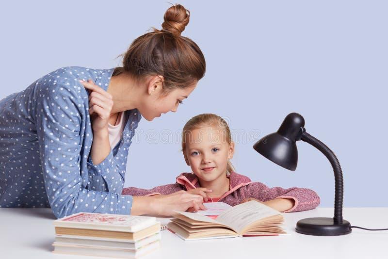 A menina encantador pequena de sorriso senta-se na tabela e sua mãe para ajudá-la a fazer a tarefa dos trabalhos de casa, tenta a fotografia de stock royalty free