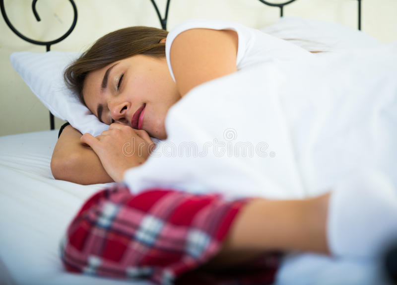 Menina encantador que dorme na cama em casa imagem de stock