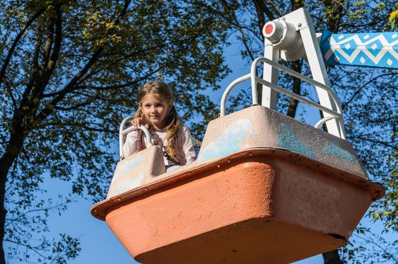 Menina encantadora caminha em um balançar em um parque de diversões imagem de stock
