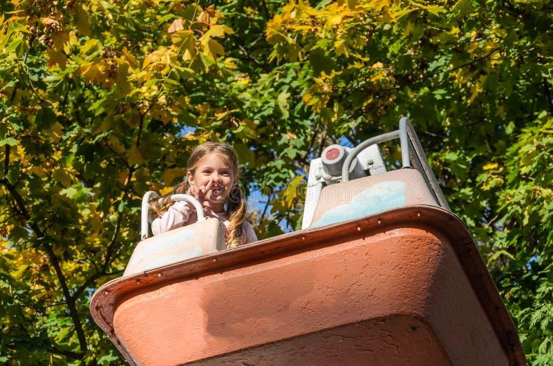 Menina encantadora caminha em um balançar em um parque de diversões fotografia de stock