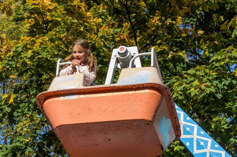 Menina encantadora caminha em um balançar em um parque de diversões imagem de stock royalty free