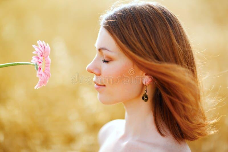 Menina encantadora com uma flor em um campo do verão imagem de stock