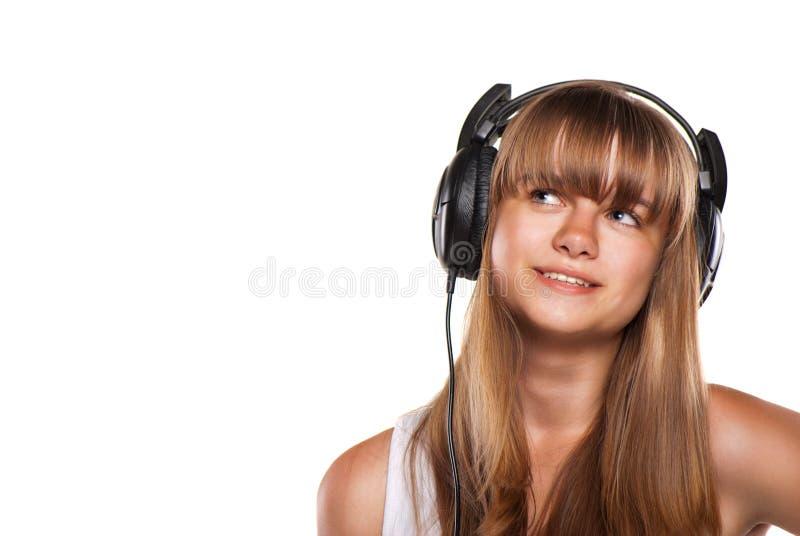 Menina encantadora que escuta uma música nos auscultadores foto de stock