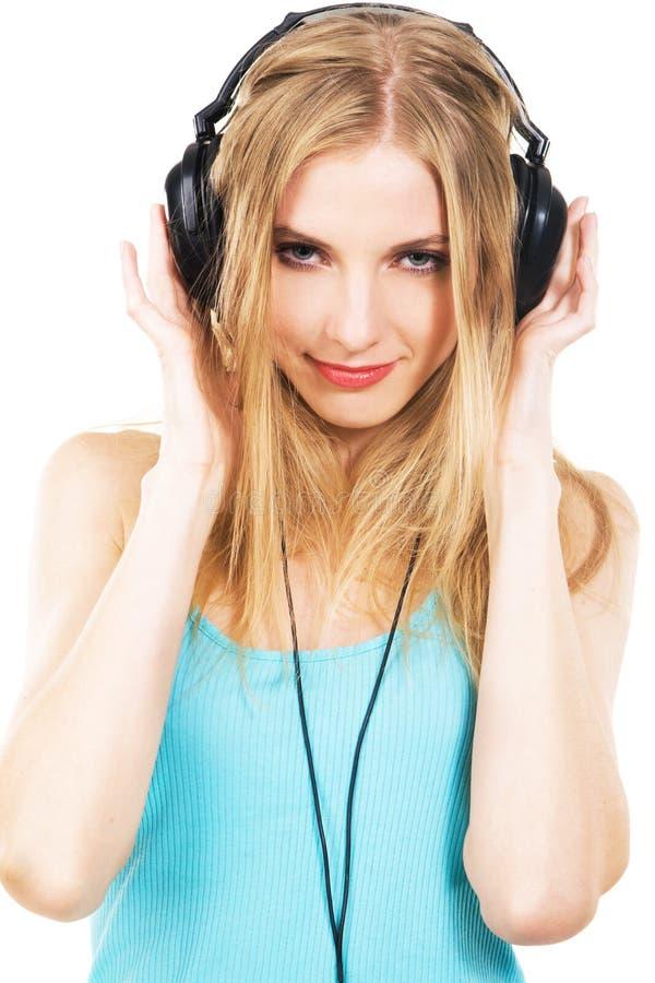 Menina encantadora que escuta uma música nos auscultadores fotos de stock
