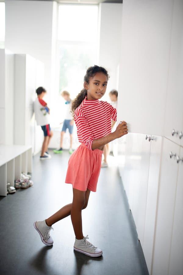Menina encaracolada com roupas cor-de-rosa parada perto do armário fotos de stock royalty free