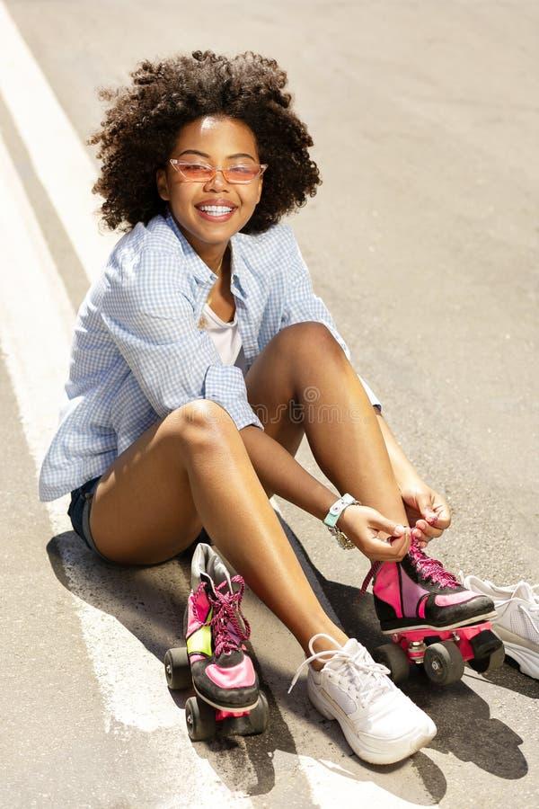 Menina encaracolado alegre que amarra laços de patins de rolo fotografia de stock royalty free
