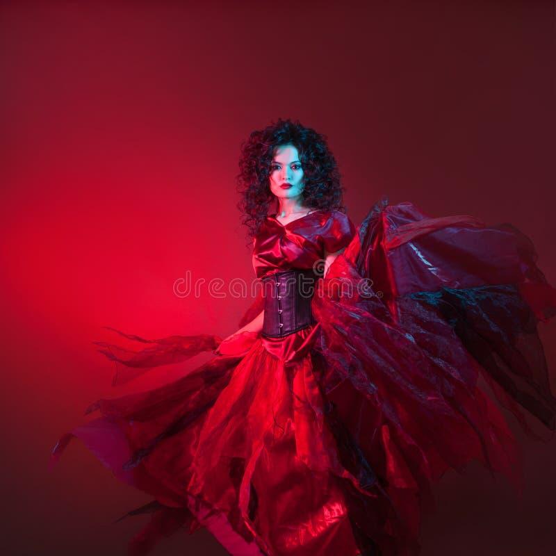 Menina encaracolado atrativa na dança vermelha do vestido em escuro - fundo vermelho, retrato no estúdio com tonificação brilhant foto de stock
