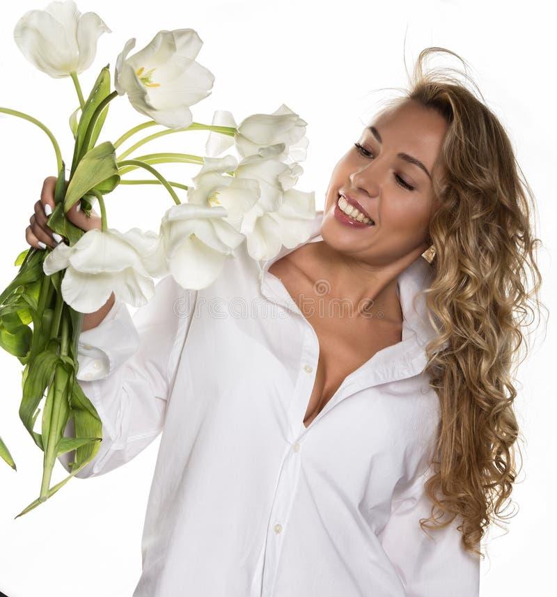 A menina encaracolado bonita com mola floresce tulipas em um fundo branco foto de stock