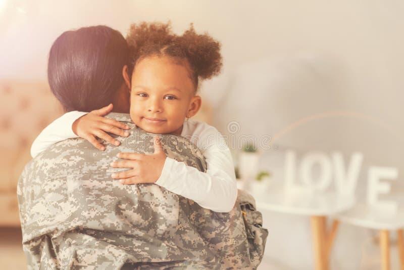 Menina encaracolado bonito que abraça sua mãe no uniforme militar fotos de stock royalty free
