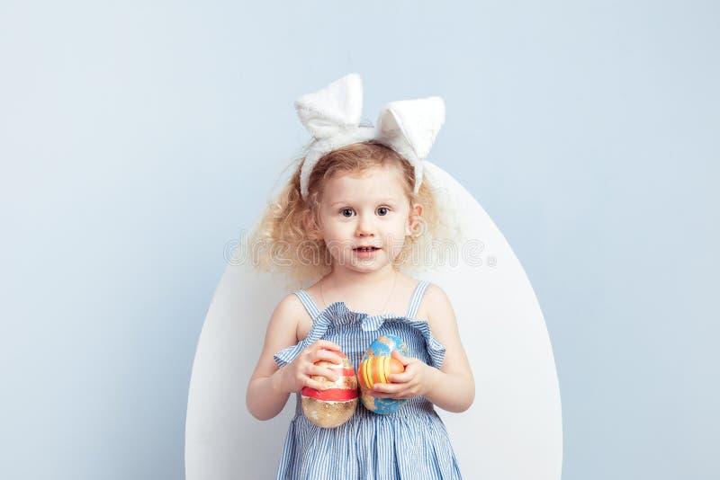 A menina encaracolado de encantamento no vestido luz-azul com as orelhas do coelho em sua cabeça guarda os ovos tingidos em suas  imagens de stock royalty free