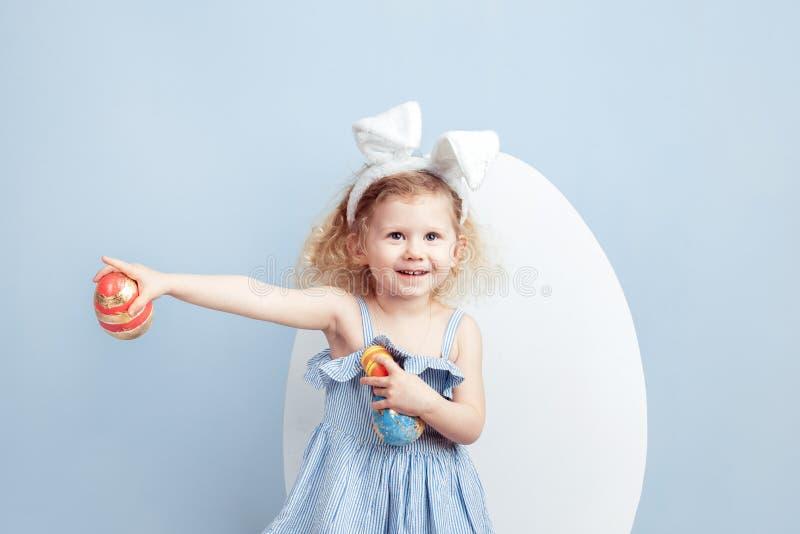 A menina encaracolado de encantamento no vestido luz-azul com as orelhas do coelho em sua cabeça guarda os ovos tingidos em suas  imagem de stock