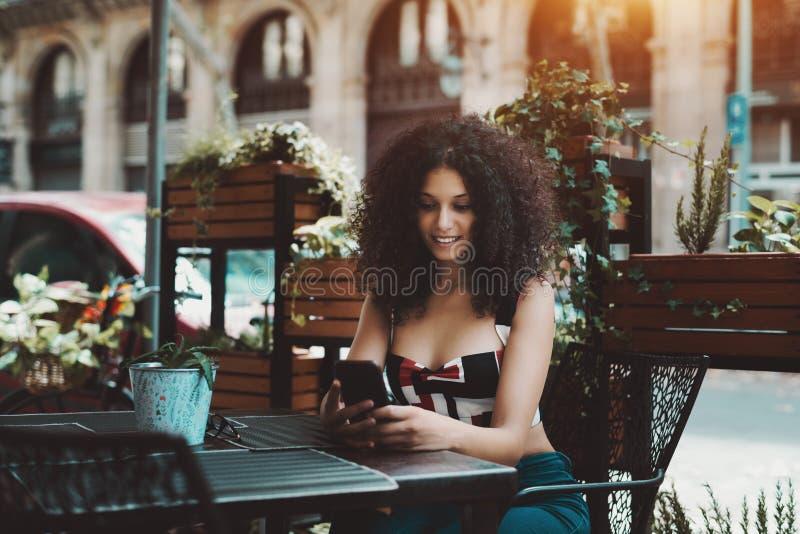 Menina encaracolado de sorriso em um café exterior usando seu telefone celular imagem de stock