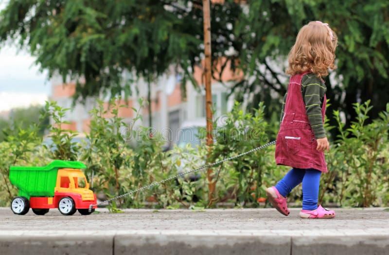 Menina encaracolado do bebê de um ano que puxa um caminhão colorido grande imagem de stock royalty free