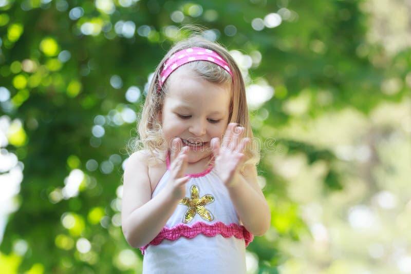 Menina encaracolado feliz da criança que aplaude com suas palmas imagem de stock