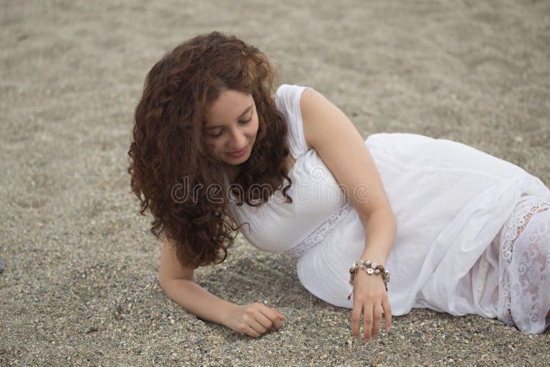 Menina encaracolado nova que joga com o seixo fotografia de stock royalty free