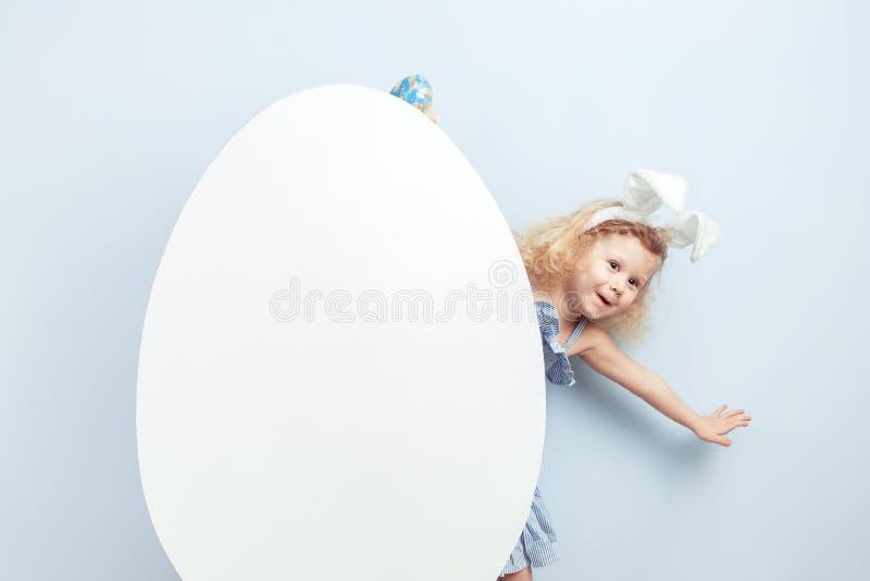 A menina encaracolado pequena no vestido luz-azul com as orelhas do coelho em sua cabeça olha para fora atrás de um ovo branco gr imagens de stock