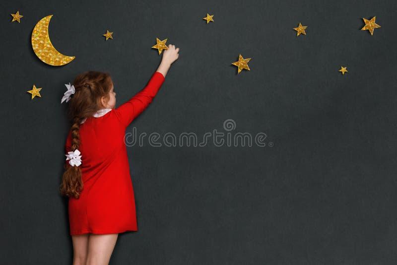 A menina encaracolado pequena no vestido vermelho alcança para fora para as estrelas e o m imagem de stock