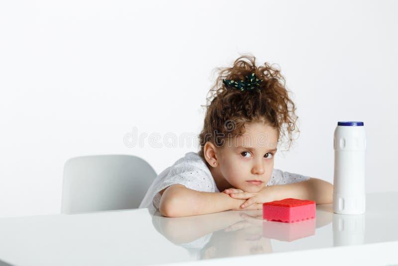 Menina encaracolado pequena triste, assentada com os braços na tabela, perto dos produtos de limpeza, sobre o fundo branco Copie  imagens de stock royalty free
