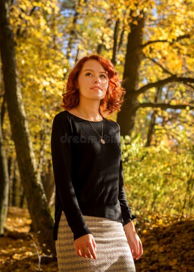 Menina encaracolado ruivo que anda na floresta do outono imagem de stock royalty free