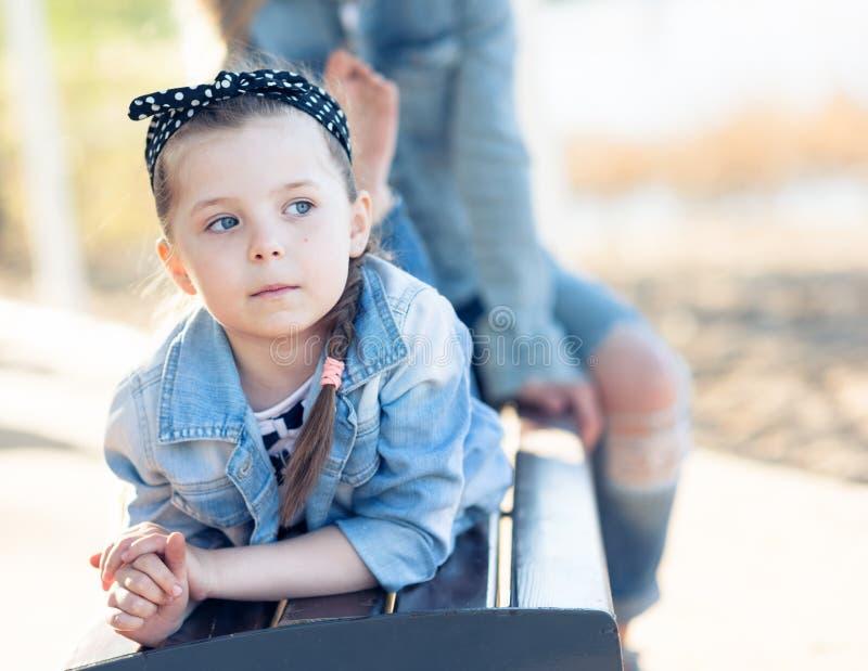 A menina encontra-se em um banco e em um sonho fotografia de stock royalty free