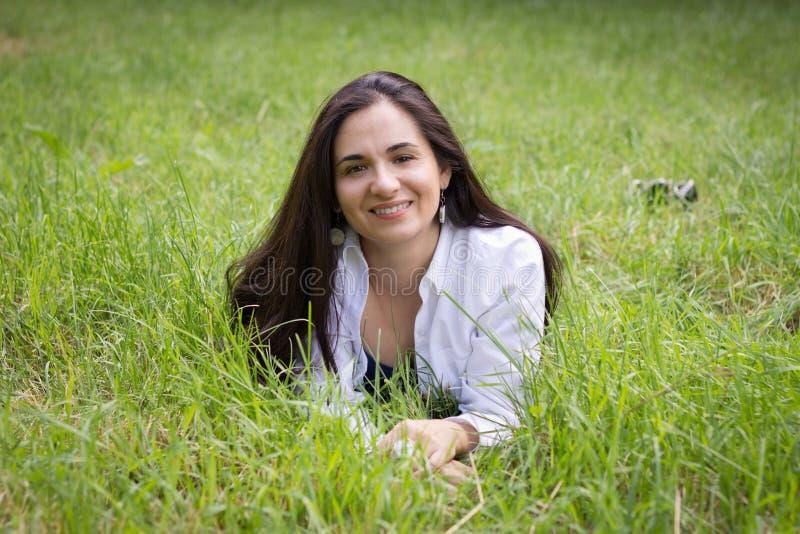 A menina encontra-se em uma grama verde imagem de stock