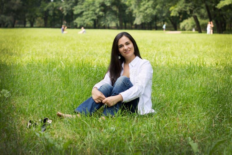 A menina encontra-se em uma grama verde fotos de stock royalty free