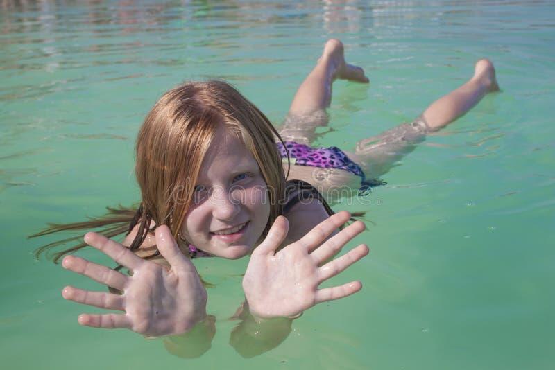 A menina encontra-se na água no Mar Morto imagens de stock
