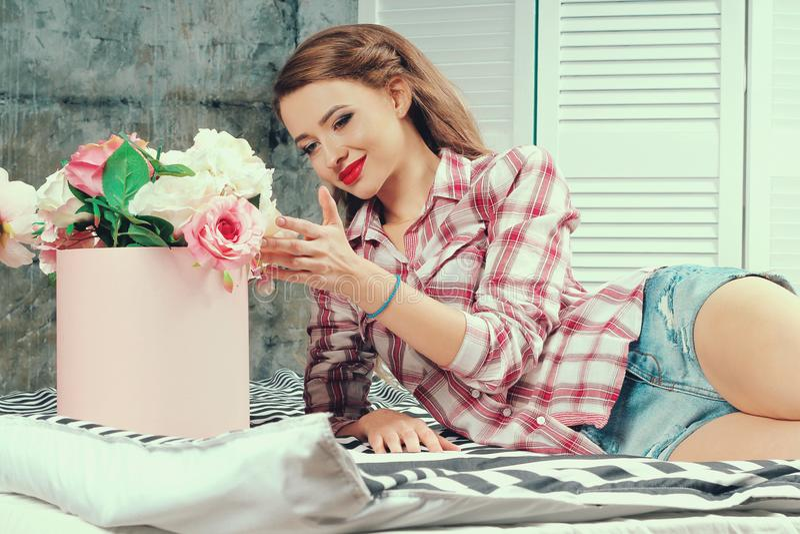 A menina encontra-se na cama e toca-se nas flores fotos de stock