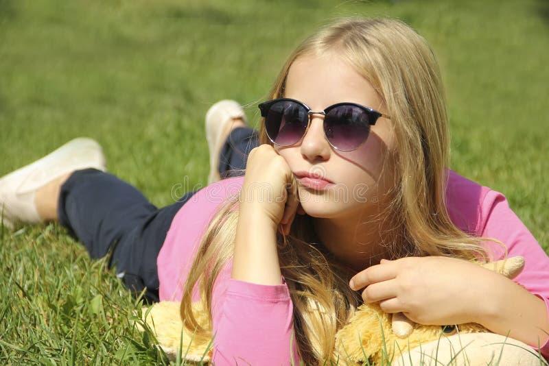 A menina encontra-se na grama com vidros fotografia de stock royalty free
