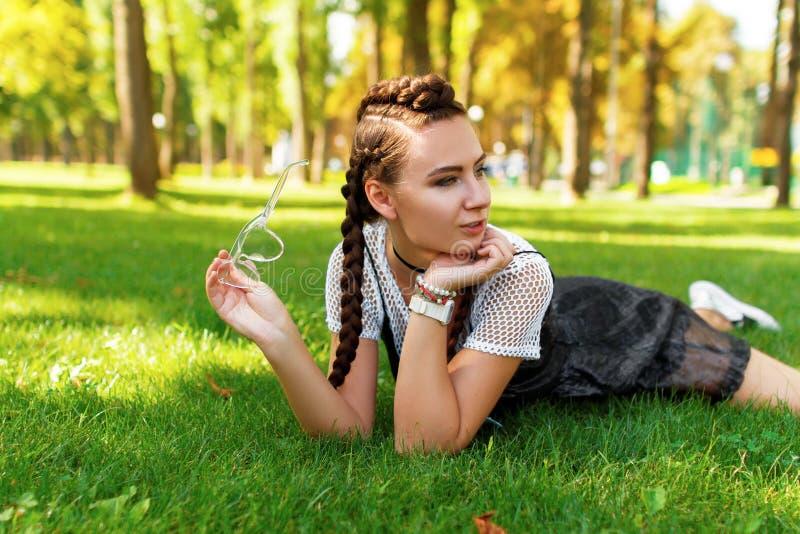 A menina encontra-se na grama no parque com os óculos de sol em sua mão fotos de stock