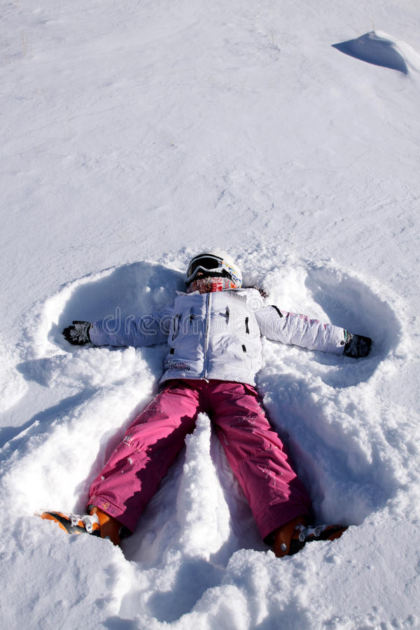 A menina encontra-se na neve. Anjo da neve foto de stock royalty free