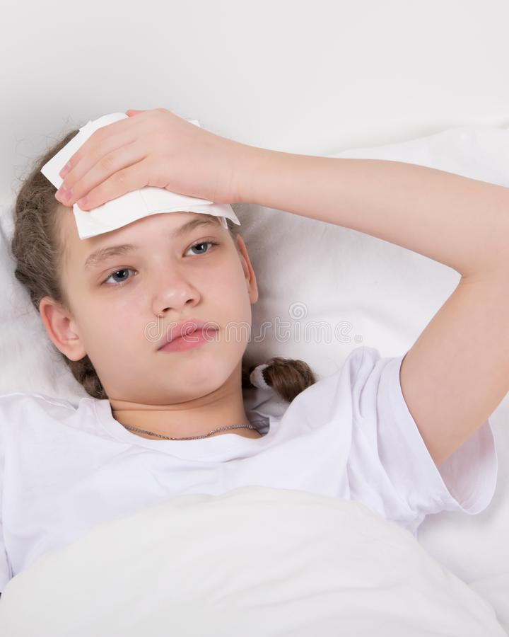 A menina encontra-se no descanso e aferra-se à cabeça doente fotos de stock royalty free