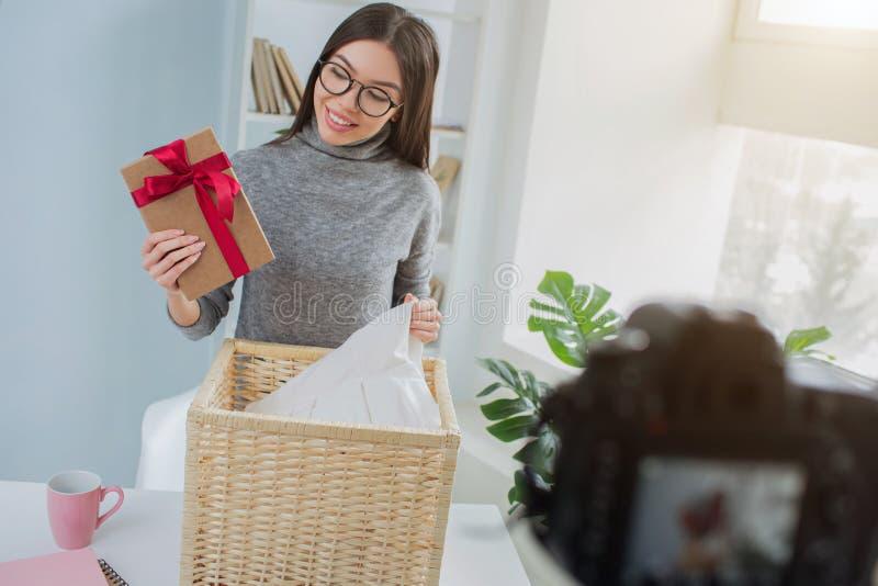 A menina encontrou um presente na cesta com lavanderia Olha surpreendida e feliz O blogger está gravando-a fotos de stock royalty free