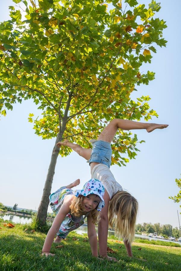 A menina engraçada é contratada na ioga com seu mothe novo desportivo imagens de stock