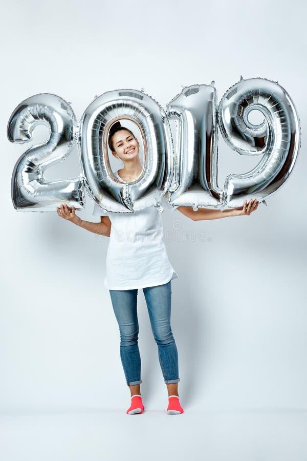 Menina engraçada agradável vestida no t-shirt branco, nas calças de brim e nas peúgas cor-de-rosa guardando balões na forma dos n imagem de stock royalty free