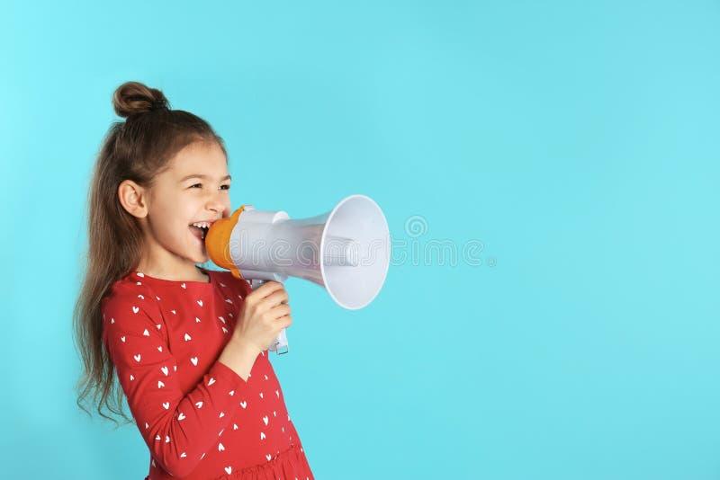 Menina engraçada bonito com o megafone no fundo da cor fotografia de stock