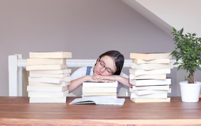 Menina engraçada bonito do tween nos vidros cansados de ler e de estudar o sono pacificamente com sua cabeça em livros entre a pi fotografia de stock