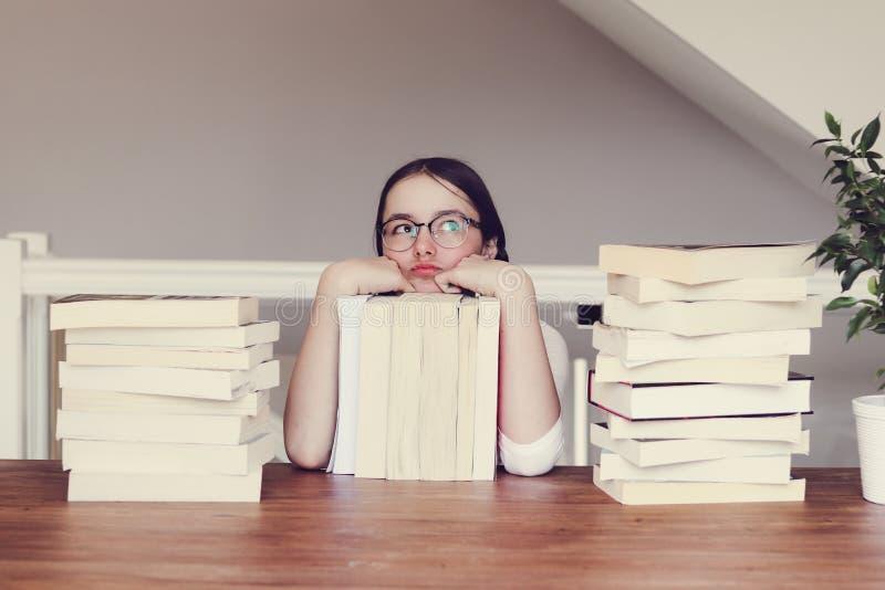 Menina engraçada bonito do tween nos vidros que sentam uma tabela com a pilha dos livros que olham cèptica e que sonham acordado  imagens de stock royalty free