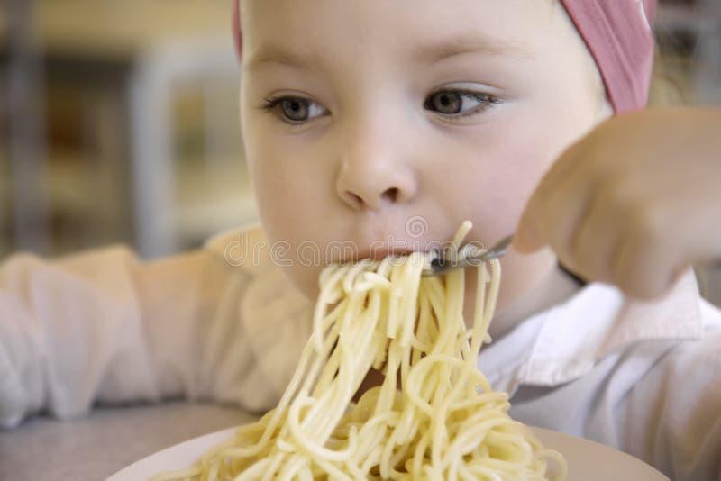 Menina engraçada bonito que come os espaguetes em casa fotos de stock