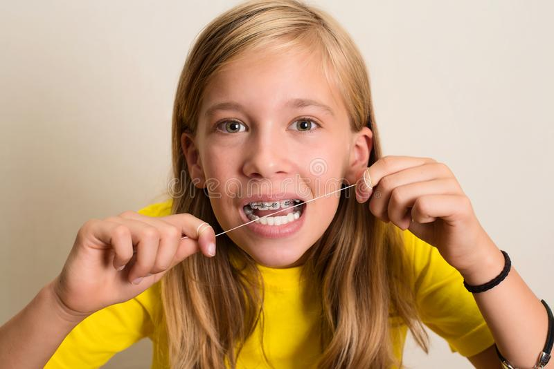 Menina engraçada com as cintas dentais que flossing seus dentes Portr do close-up fotos de stock royalty free