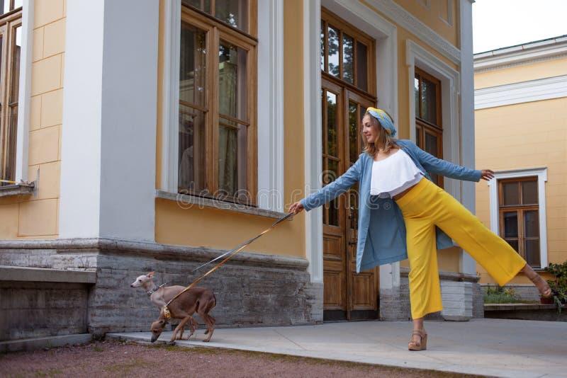 Menina engraçada com o cão em uma caminhada fotografia de stock