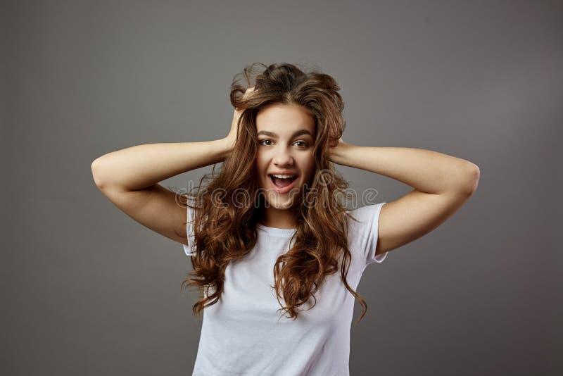 A menina engraçada com o cabelo marrom longo vestido em um t-shirt branco guarda suas mãos em sua cabeça no estúdio no cinza fotos de stock royalty free