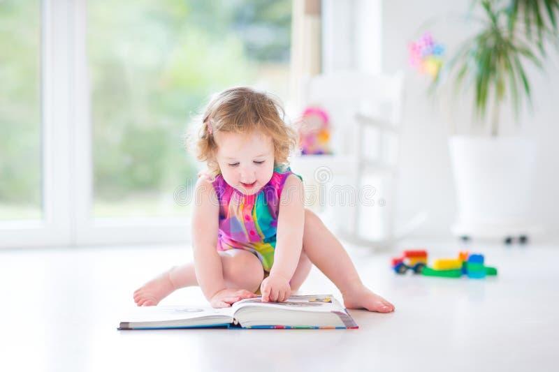Menina engraçada da criança que lê um livro que senta-se em um fllor foto de stock royalty free