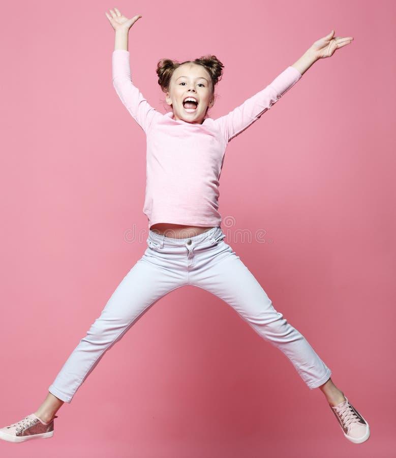 a menina engraçada da criança vestiu o salto ocasional no fundo cor-de-rosa foto de stock royalty free